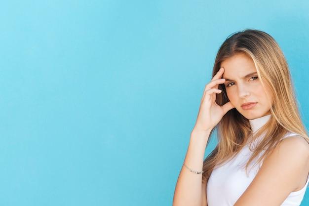 Mujer joven rubia preocupada contra fondo azul