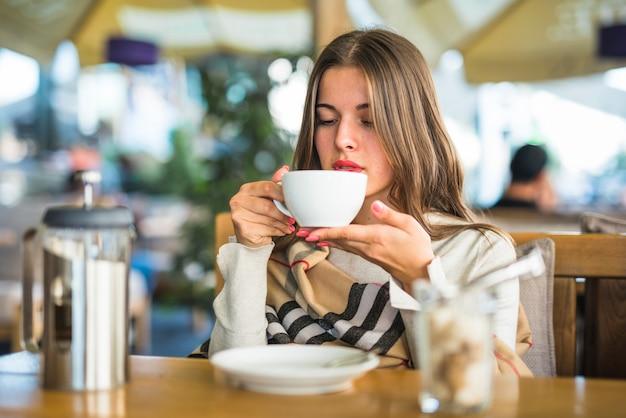 Mujer joven rubia que bebe té herbario en la taza blanca