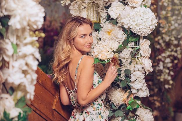 Mujer joven rubia que se coloca cerca de la decoración de la flor blanca