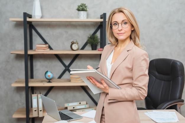 Mujer joven rubia que se coloca delante del escritorio de oficina que escribe en el cuaderno espiral