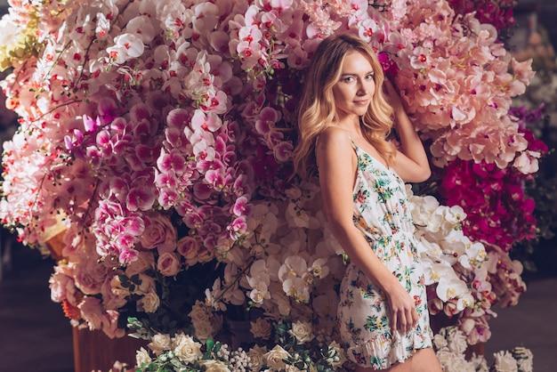 Mujer joven rubia que se coloca delante de las flores artificiales coloridas de las orquídeas