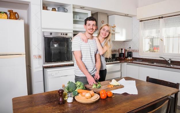 Mujer joven rubia que se coloca con sus verduras del corte del marido en la cocina