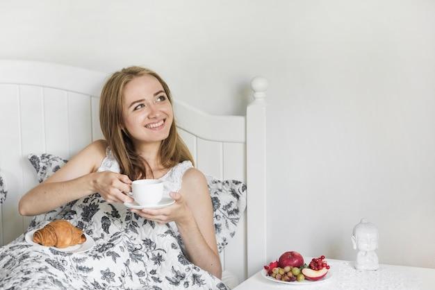 Mujer joven rubia que disfruta del desayuno de la mañana en cama
