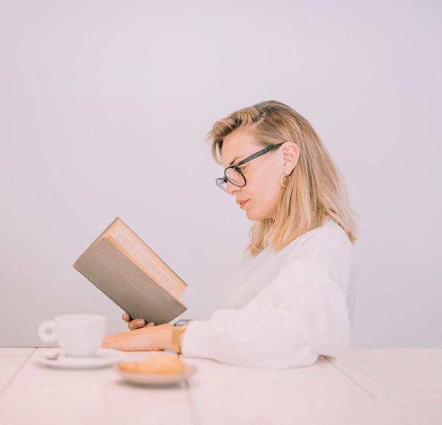 Mujer joven rubia que lee el libro con café y bocado en la tabla blanca