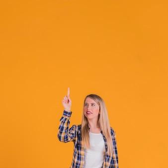 Mujer joven rubia que señala su dedo hacia arriba contra un fondo naranja