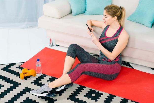 Mujer joven rubia que se sienta en la alfombra en casa usando el teléfono móvil