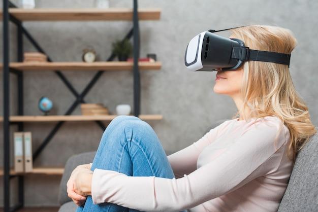 Mujer joven rubia que se sienta en el sofá que lleva gafas de la realidad virtual