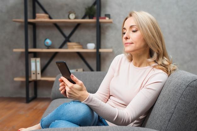 Mujer joven rubia que se sienta en el sofá usando el teléfono elegante en casa
