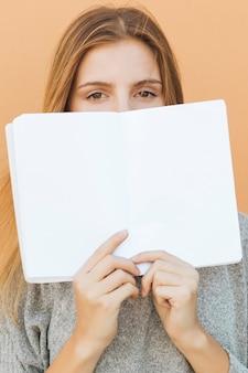 Mujer joven rubia que sostiene el libro en blanco sobre su boca contra el contexto del melocotón