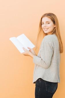 Mujer joven rubia que sostiene el libro a disposición que mira la cámara contra fondo del melocotón
