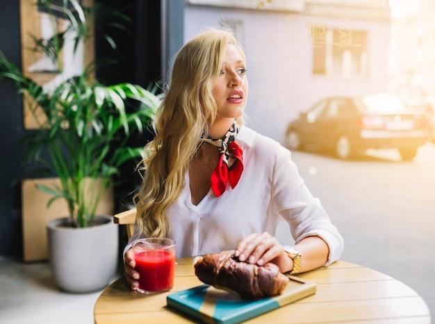 Mujer joven rubia que sostiene el pan y el vidrio de jugo en la mano que mira lejos