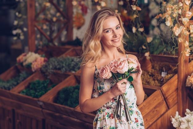 Mujer joven rubia que sostiene las rosas rosadas en la mano que se coloca en floristería