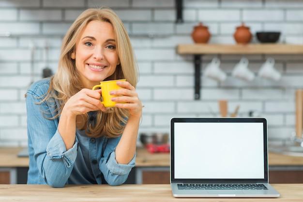 Mujer joven rubia que sostiene la taza de café con el ordenador portátil en la tabla de madera