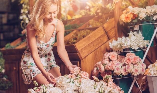 Mujer joven rubia que toca las rosas en la floristería