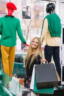 Mujer joven rubia sonriente que se coloca delante de la exhibición de la ventana que sostiene bolsos de compras coloridos