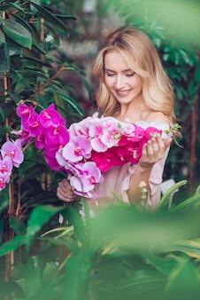 Mujer joven rubia sonriente que se coloca delante de las plantas verdes que miran las flores rosadas exóticas de la orquídea