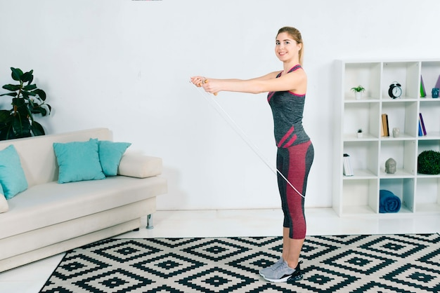 Mujer joven rubia sonriente que ejercita con la cuerda que salta en casa en la sala de estar