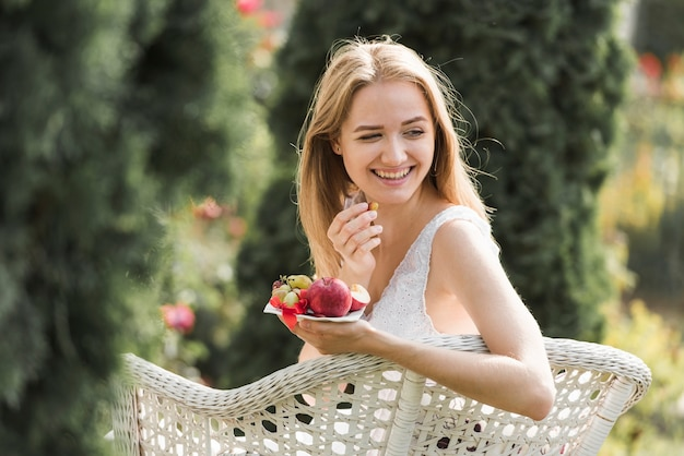 Mujer joven rubia sonriente que se sienta en la silla que come las frutas en el jardín