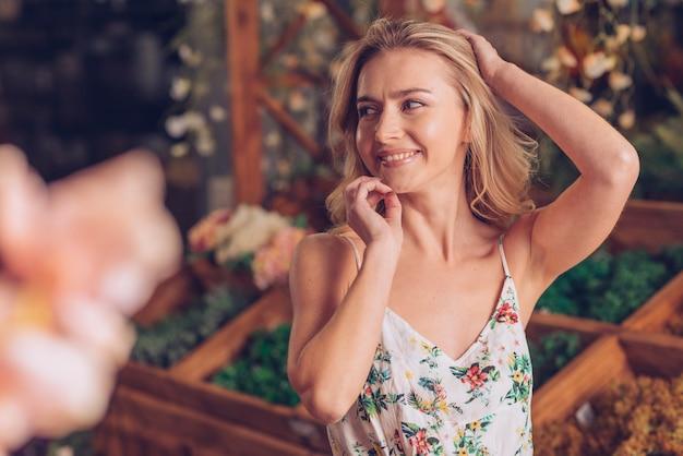 Mujer joven rubia tímida con la mano en su cabeza que se coloca en el jardín