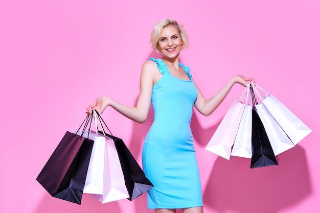 Mujer joven rubia con un vestido azul tiene bolsas de la compra sobre un fondo de color rosa