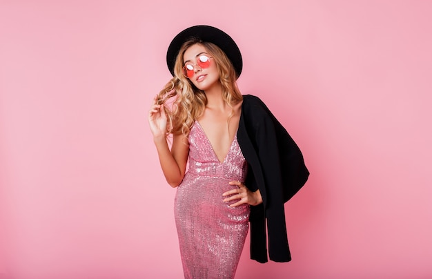 Mujer joven rubia en vestido increíble con lentejuelas y gafas redondas moda posando juguetonamente en la pared de color rosa.