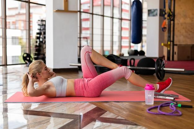 Mujer joven en rutina de ejercicios mat