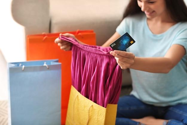 Mujer joven sacando la falda de la bolsa de compras en casa
