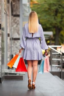 Mujer joven saliendo de la tienda de compras