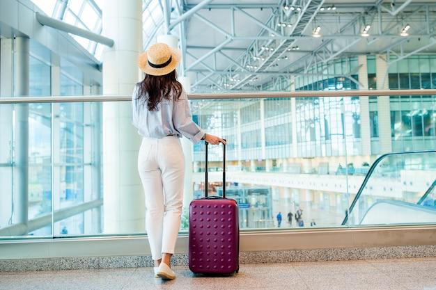 Mujer joven en un salón del aeropuerto esperando el avión de vuelo.