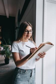 Mujer joven en salón de negocios, tomando notas en un bloc de notas.