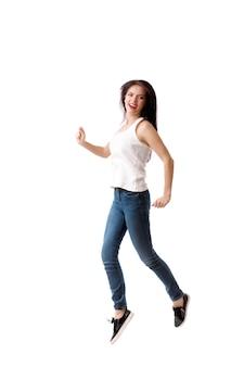 La mujer joven está saltando en blanco