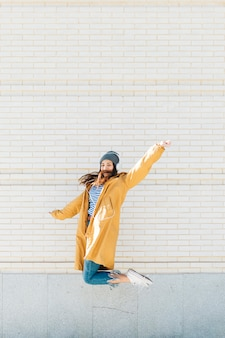 Mujer joven saltando contra la pared de ladrillo usando auriculares