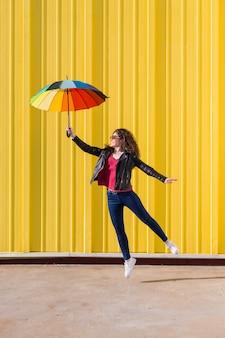 Mujer joven saltando y divirtiéndose con un colorido paraguas sobre amarillo