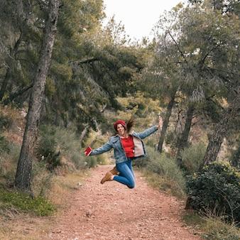 Mujer joven saltando por encima del sendero en la montaña