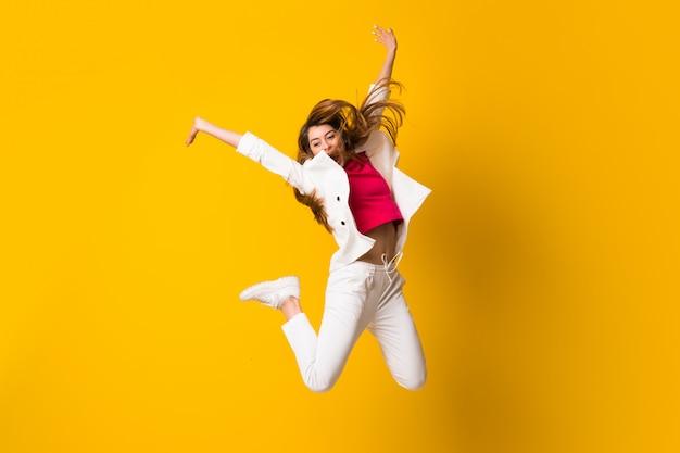 Mujer joven saltando sobre pared amarilla aislada