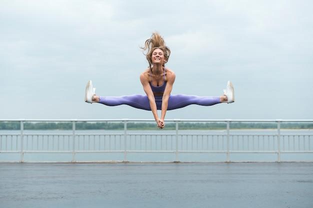 Mujer joven, saltar, tiro largo