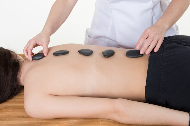 Mujer joven y saludable en el salón de spa con masaje con piedras calientes
