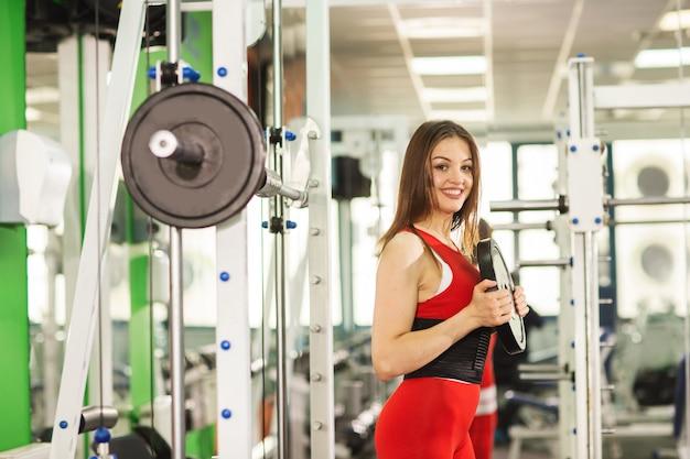 Mujer joven sana con barra, en un traje deportivo rojo, posando en el gimnasio