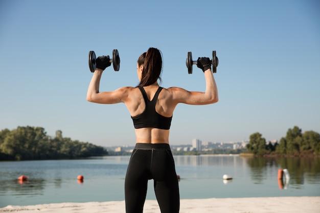 Mujer joven sana formación de la parte superior del cuerpo con pesas en la playa.