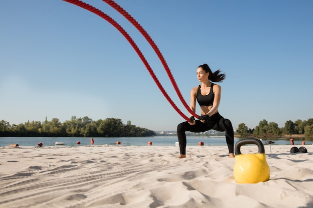 Mujer joven sana haciendo ejercicio con las cuerdas en la playa.