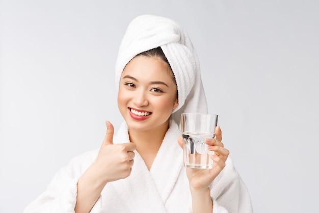 Mujer joven sana hermosa agua potable, maquillaje natural de cara de belleza, aislado sobre
