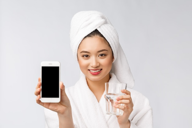 Mujer joven sana hermosa agua potable, maquillaje natural de la cara de belleza con la celebración de teléfono móvil, aislado sobre