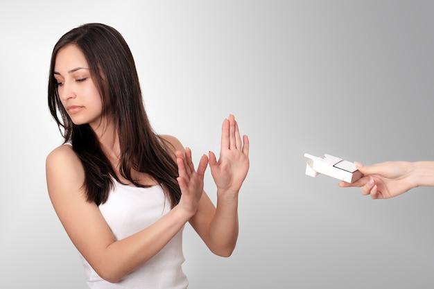 Mujer joven sana que se niega a tomar cigarrillos del paquete. retrato de hermosa mujer mostrando parada.