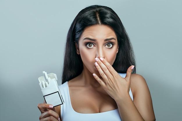 Mujer joven sana que se niega a tomar cigarrillos del paquete