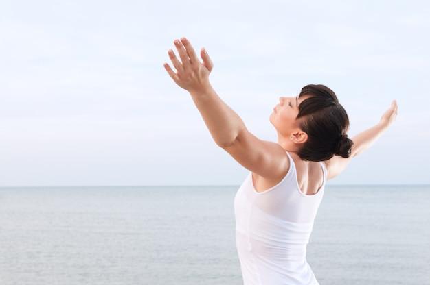 Mujer joven sana que respira y disfruta de la brisa del verano al aire libre en el mar