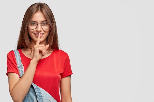 Mujer joven satisfecha con expresión complacida, le dice el secreto a su mejor amiga, hace un gesto de silencio, vestida con una camiseta roja informal y un peto de mezclilla, aislado sobre una pared blanca con espacio de copia