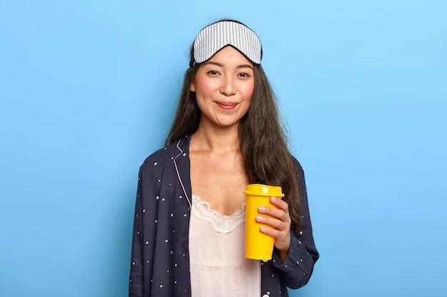 Mujer joven satisfecha usa antifaz y ropa de dormir, intenta refrescarse con aromático café para llevar, disfruta de tiempo para descansar