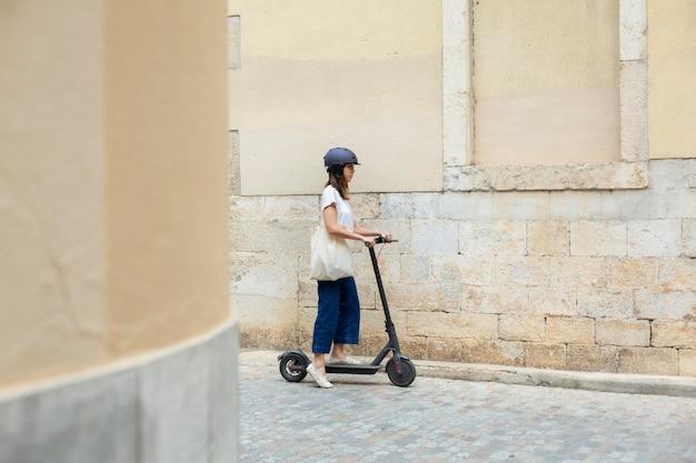 Mujer joven con un scooter ecológico