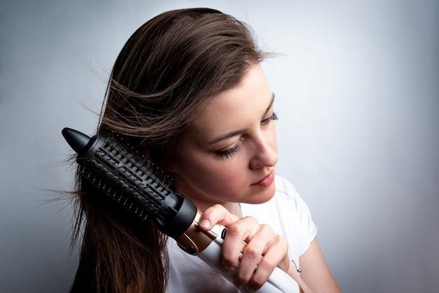 Mujer joven con secador de pelo y peine cepillándose el pelo.