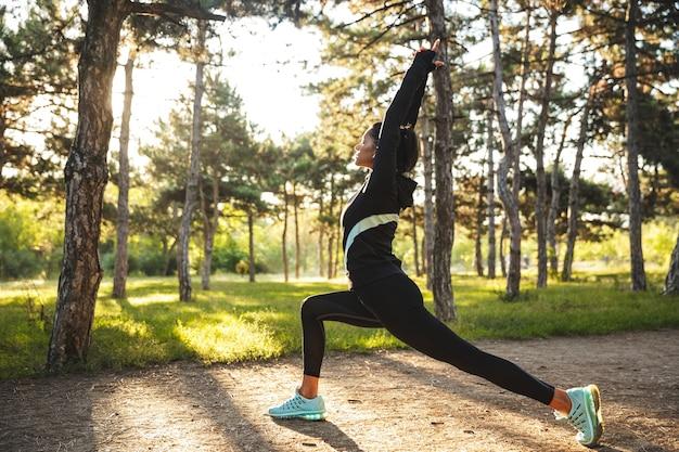Mujer joven segura de deportes calentando antes de trotar en el parque, escuchando música con auriculares inalámbricos